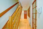 Hallway with hardwood staircase to upper floor